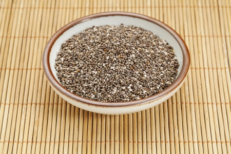 chia seeds in a ceramic  bowl against bamboo mat