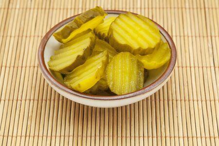 竹マットのキュウリのピクルスのスライスを醤油皿