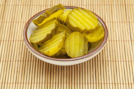 sauce dish with slices of cucumber pickles on a bamboo mat Stock Photo - 17668256
