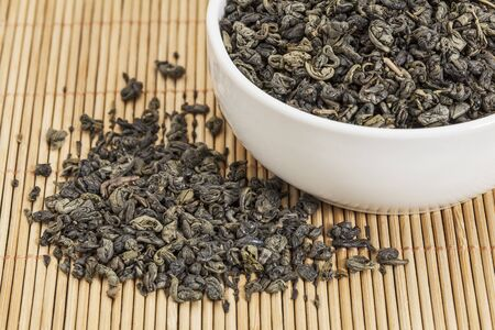 loose leaf gunpowder green tea in a white china cup and spilled over bamboo mat Stock Photo - 17668259