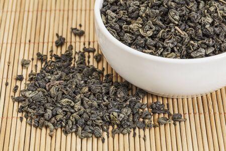 gunpowder tea: loose leaf gunpowder green tea in a white china cup and spilled over bamboo mat
