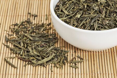 sencha tea: loose leaf Sencha green tea in a white china cup and spilled over bamboo mat Stock Photo