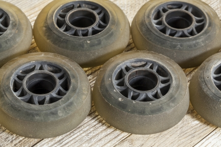 inline skating: old worn out wheels for inline skating on wooden surface