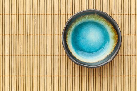 small empty ceramic bowl (sauce dish) with blue enamel on bamboo placemat Stock Photo - 17806560