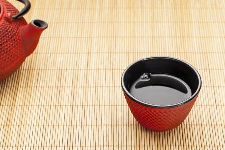japones bambu: Taza de té japonés con un tetsubin en una estera de bambú - una plancha tradicional reparto rojo diseño clavo con esmalte negro en el interior Foto de archivo