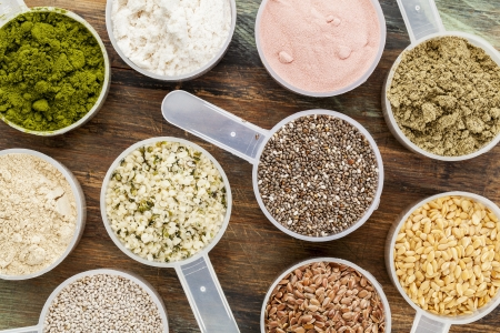 scoops of superfood - healthy seeds and powders (white and brown chia, brown and golden flax, hemp, pomegranate fruit powder, wheatgrass, hemp and whey protein, maca root) - top view Stock Photo
