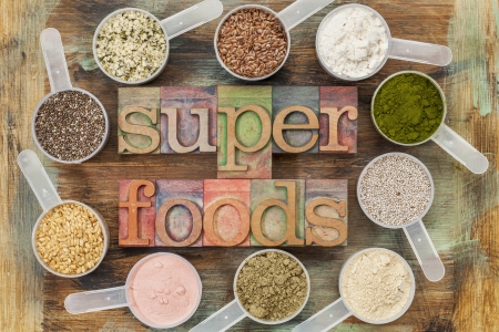 whey: superfoods word in letterpress wood type surrounded by plastic scoops of healthy seeds and powders (chia, flax, hemp, pomegranate fruit powder, wheatgrass,  whey protein, maca root) - top view