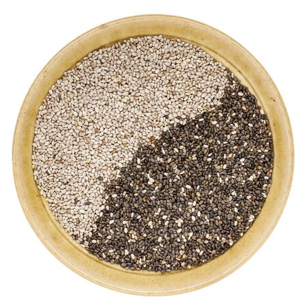 chia seed: black and white chia seeds in a small ceramic bowl isolated on white Stock Photo