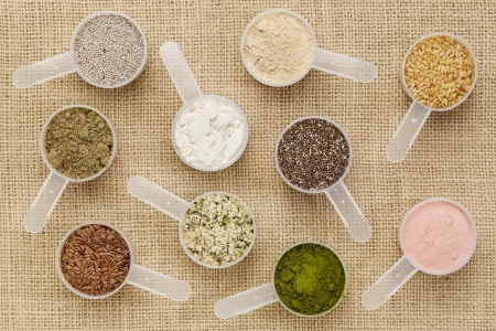 scoops of superfood - healthy seeds and powders (white and black chia, flax, hemp, pomegranate fruit powder, wheatgrass, hemp and whey protein, maca root) on canvas Stock Photo - 17806576