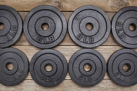 background of exercise weights -  iron dumbbell plates on a wooden deck Stock Photo - 17959941