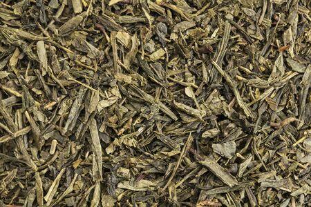 sencha tea: background texture of Sencha green tea - fresh, sweet, delicate tea presented as slender, needle-shaped leaves from the famous Fuji district of Shizuoka, Japan.