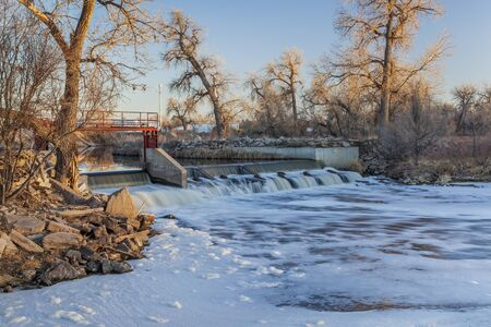 south platte river: small river dam diverting water to farmland irrigation - South Platte River near Fort Lupton, Colorado, winter scenery at sunset