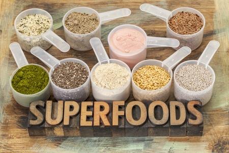 hemp: superfoods word in letterpress Holz mit Kunststoff-Kugeln von gesunden Samen und Pulver (chia, Flachs, Hanf, Granatapfel Pulver, Weizengras, Maca-Wurzel) Lizenzfreie Bilder