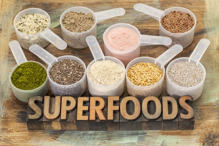 superfoods word in letterpress wood type with plastic scoops of healthy seeds and powders (chia, flax, hemp, pomegranate fruit powder, wheatgrass, maca root) Stock Photo