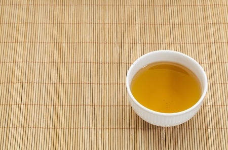 white china cup of green tea against bamboo place mat Stock Photo - 18024317