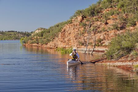 canoe paddler (senior male) on a mountain lake - Horsetooth Reservoir near Fort Collins, Colorado at springtime photo