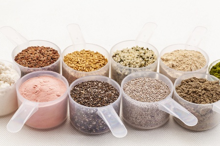 scoops of superfood - healthy seeds and powders (white and black chia, flax, hemp, pomegranate fruit powder, wheatgrass,whey protein, maca root) on white tablecloth Stock Photo - 18083303