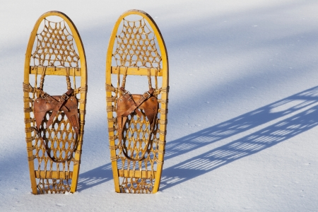 a pair of classic Bear Paw wooden snowshoes cast shadow in snow Stock Photo - 18133756