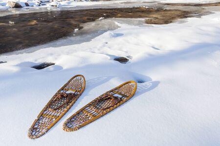 poudre river: classic wooden Bear Paw snowshoes on the shore of partially frozen Cache la Poudre River near Fort Collins, Colorado