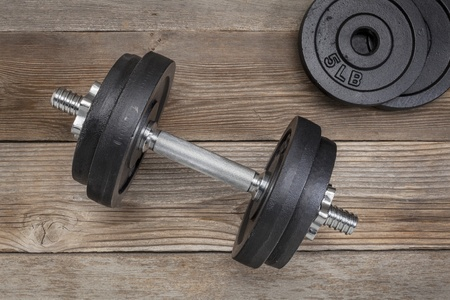 exercise weights - iron dumbbell with extra plates on a wooden deck Stock Photo - 18169268