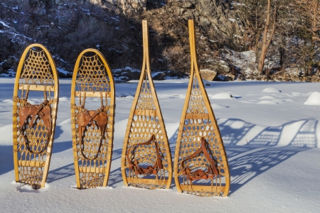 snowshoe: vintage Bear Paw and Huron snowshoes cast shadow in snow, Poudre River Canyon near Fort Collins, Colorado
