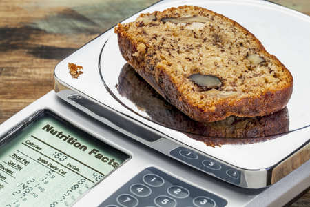 slice of banana bread with walnuts on diet scale displaying nutrition facts - a diet concept Stock Photo - 18224156