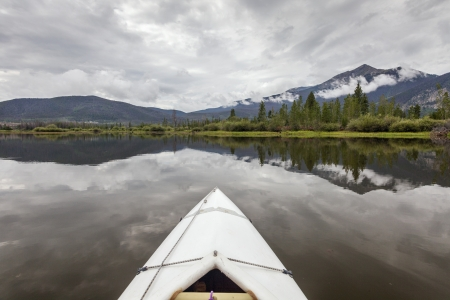 lake dillon: bow of a white kayak on Lake Dillon in Colorado Rocky Mountains, cloudy sky with water reflections