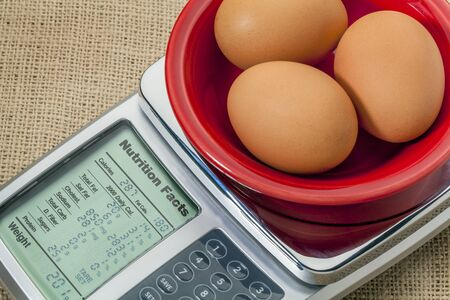 three eggs on diet scale displaying nutrition facts - a diet concept Stock Photo - 18286913