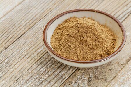 superfruit: raw organic dried camu camu fruit powder (Myciara Dubia) in a small ceramic bowl - rainforest superfruit from Peru rich in vitamin C Stock Photo