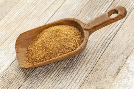 coconut palm sugar: a wooden rustic scoop of unrefined coconut palm sugar against a white painted grunge wood background