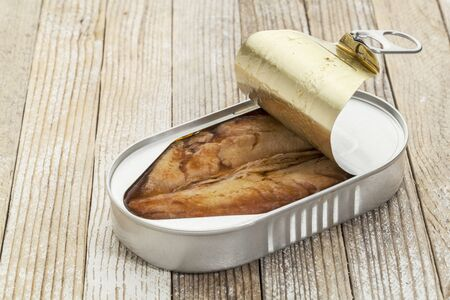 open can of wild herring in wine sauce against a white painted grunge background Stock Photo - 18363737