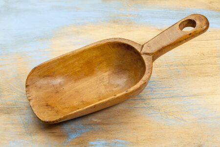 empty wooden rustic scoop on a wood cutting board with grunge blue paint Stock Photo - 18413690