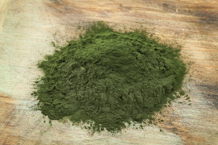 algae: a pile of Hawaiian spirulina powder on wooden surface