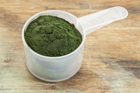 measuring scoop of Hawaiian spirulina powder against wooden background