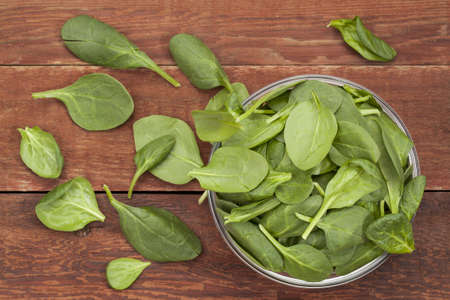 'baby spinach': baby spinach leaves spilling from a glass bowl onto red barn wood table