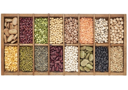 typesetter: old wooden typesetter box with 16 samples of assorted legumes: green, red and French lentils, soybean, green and yellow pea, fava bean, kidney, black, mung chickpea bean,adzuki bean Stock Photo