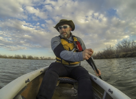 paddling: senior male paddling a canoe on calm lake in early spring in Fort Collins, Colorado, POV shot from a boat bow Stock Photo