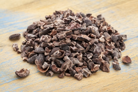 Close-up of a pile of raw cacao nibs on a grunge wooden background Reklamní fotografie