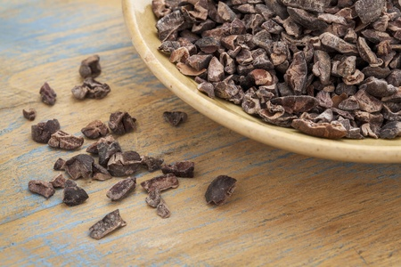 nib: Raw cacao nibs in a small ceramic bowl against grunge wooden background