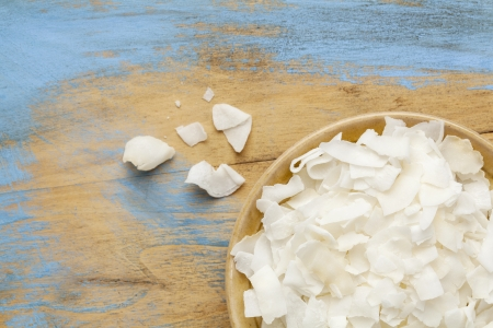 flakes of shredded coconut in a small ceramic bowls against  grunge wooden background, copy space