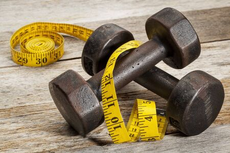 a pair of vintage iron rusty dumbbells with yellow measuring tape on white painted barn wood background - fitness concept photo