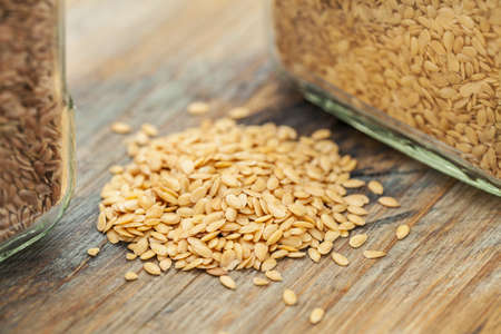 gold flax: gold flax seeds on a wood background, a small pile and glass jars with a selective focus
