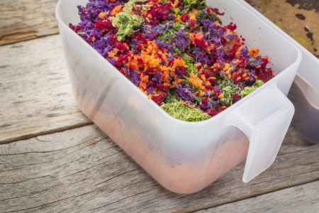 colorful juicer pulp after juicing raw vegetables (carrot, red beat, cucumber, kale, red cabbage) - a plastic cup against barn wood background Stock Photo - 18792181
