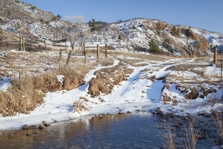 eagle nest rock: ranch road crossing stream in a mountain valley, winter scenery, Eagle Nest Rock Open Space, Larimer County, Colorado Stock Photo