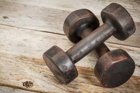 a pair of vintage iron rusty dumbbells on white painted barn wood background - fitness concept Stock Photo - 18792199