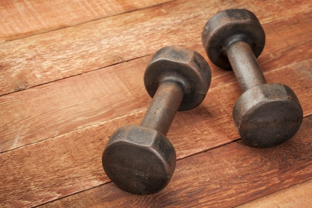 a pair of vintage iron rusty dumbbells on red barn wood background - fitness concept Stock Photo - 18792195