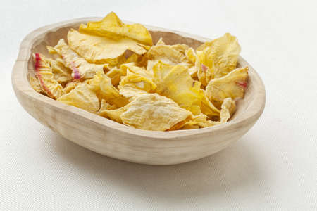 a rustic wood bowl of dried slices of yacon tuber on white tablecloth Stock Photo - 18879137