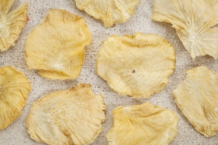 promotes: Rodajas secas de yac�n en blanco grunge pintado de madera. El yac�n contiene inulina, un az�car complejo, que promueve los probi�ticos saludables.