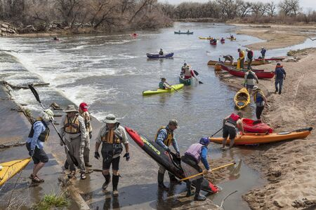 evans: SOUTH PLATTE RIVER, EVANS, COLORADO - APRIL 6: Portaging kayak and canoes over a river diversion dam during Annual All Club Paddle on April 6, 2013. It is a popular season opening paddling trip in northern Colorado.