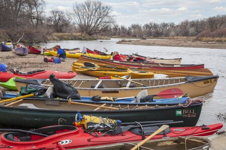 SOUTH PLATTE RIVER, EVANS, COLORADO - APRIL 6: Kayaks and canoes on a river shore during Annual All Club Paddle on April 6, 2013. It is a popular season opening paddling trip in northern Colorado. Editorial